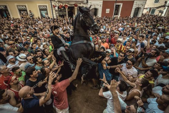 A 'caixer' (horse rider) rears up on his horse during the Gracia Festival in Mahon, Spain, Sept. 8, 2018
