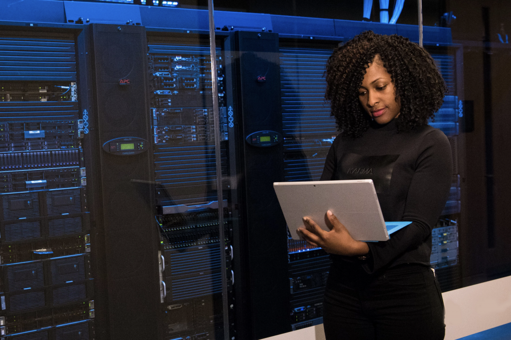 woman holding laptop in front of servers