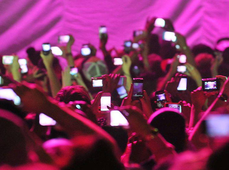 a crowd holding up their smartphones