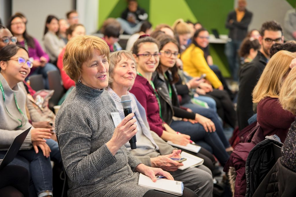 women sit in an audience, one speaks into a microphone