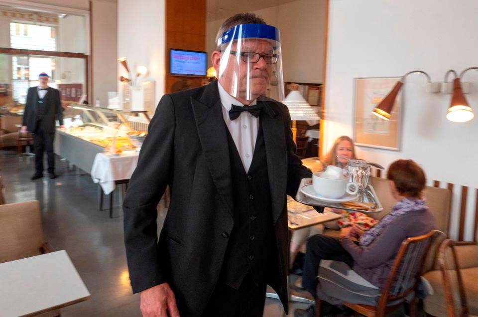 A waiter in a tux wears a face shield at an upscale restaurant
