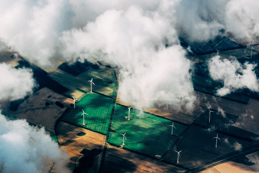 wind turbines in a field seen from above through clouds