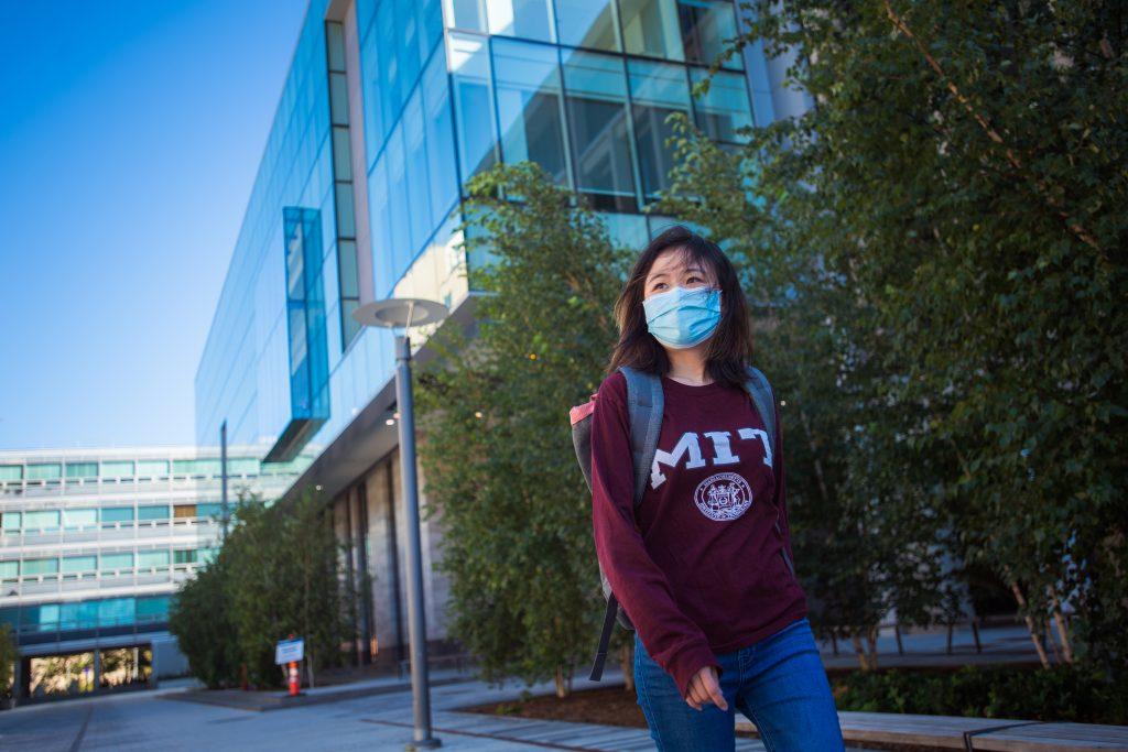 a masked student in and MIT sweatshirt walking on MIT campus