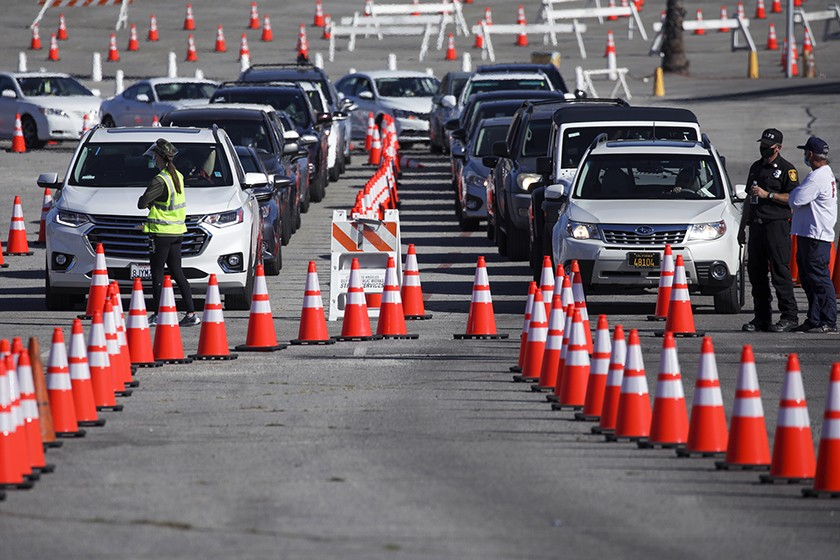 people in cars line up for COVID vaccine
