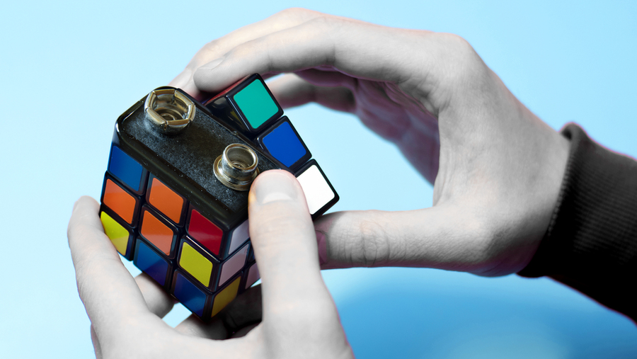 stock image of a battery as part of a rubik's cube, implying a battery puzzle