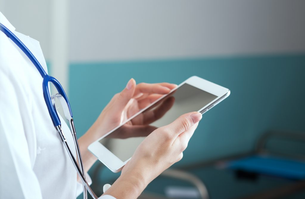 stock image of doctor using computer tablet