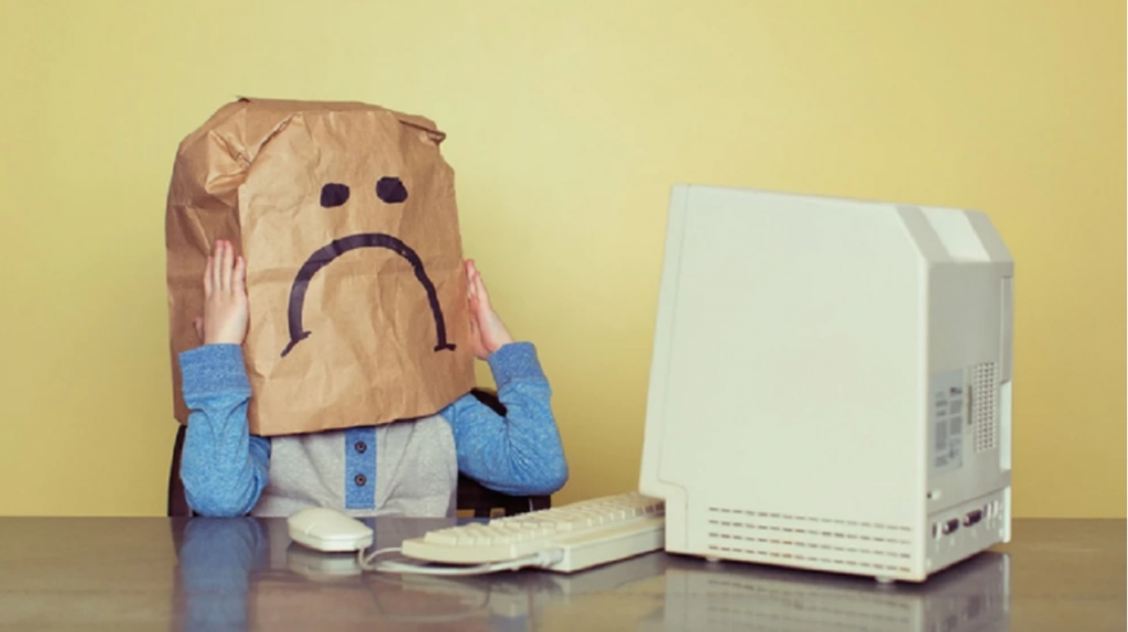 a person wearing a bag mask with a frowning face using a computer