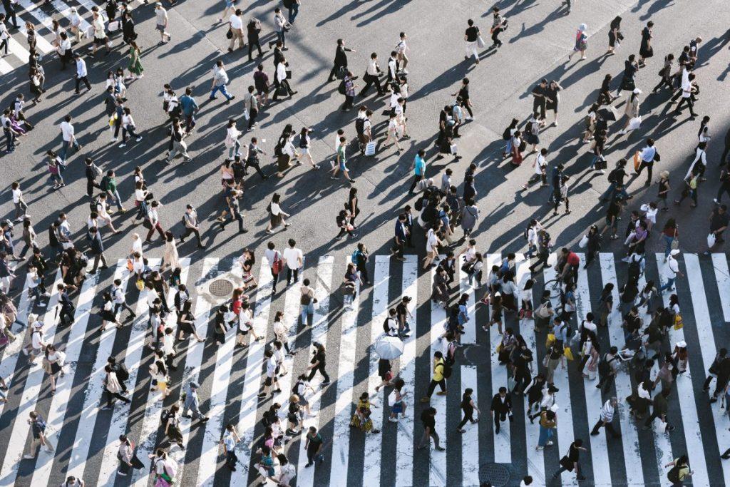 an overhead view of a crowd walking across a crosswalk