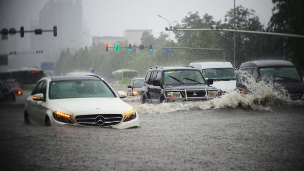 Cars attemping to drive down flooded streets