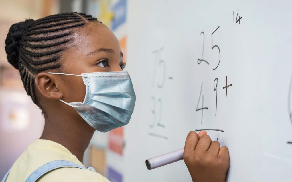 girl wearing a mask writing math equations on a white board